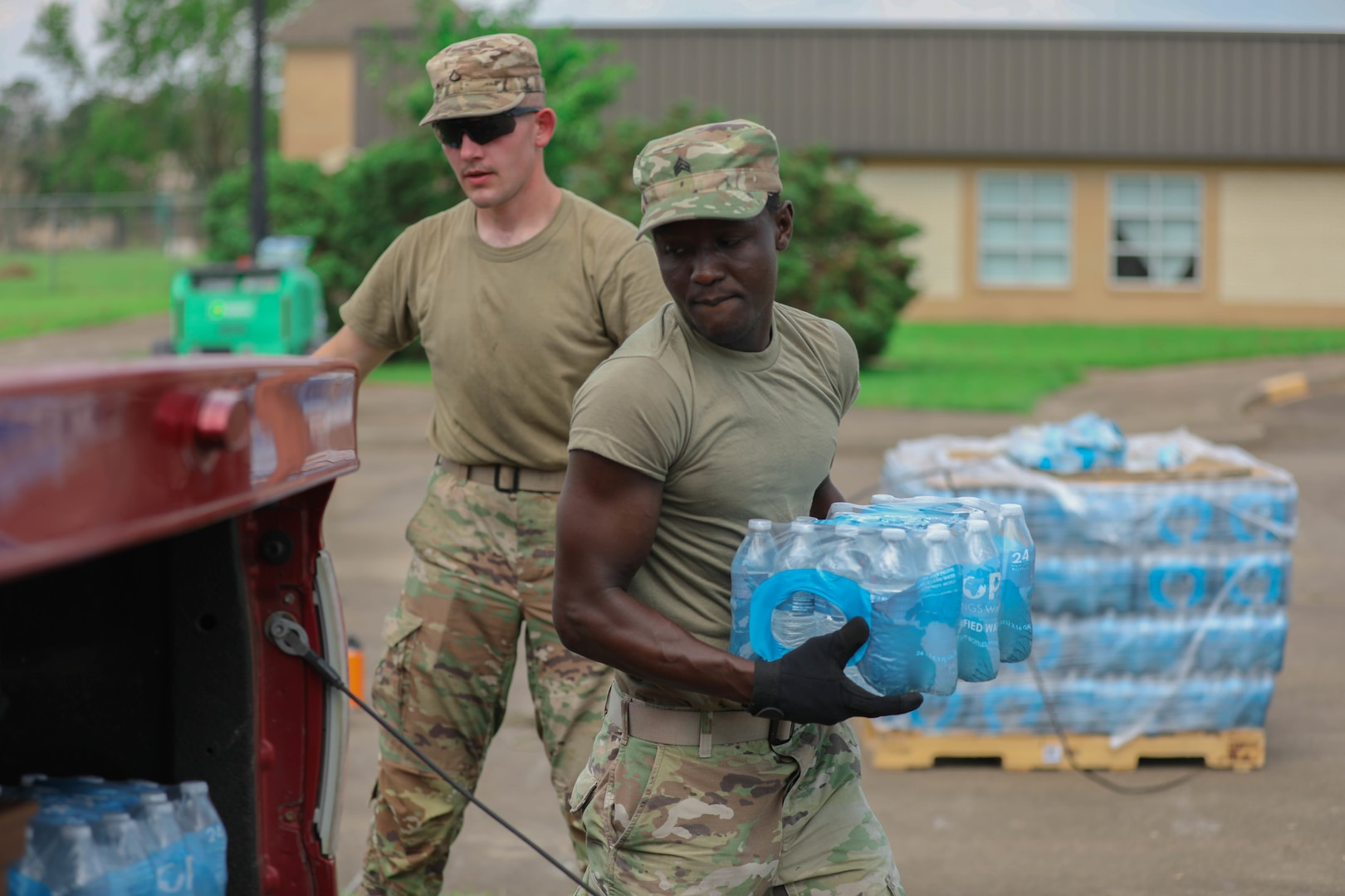 Sgt. Stephen Bruke, a Mustang, Oklahoma resident and Oklahoma Army National Guard, hands out water at a point of distribution site in Gramercy, Louisiana, Sept. 4. . The Oklahoma National Guard operates 13 PODs across seven parishes that supply local families with tarps, meals ready to eat, ice and water. (Oklahoma National Guard photo by Cpl. Reece Heck)