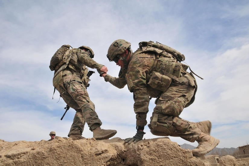 A soldier helps another soldier into a rooftop.