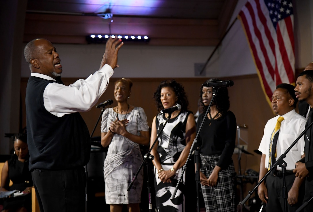 """Minister Dennis Thompson leads the Gospel Choir in a song during the 50th Gospel Worship Service Anniversary inside Larcher Chapel at Keesler Air Force Base, Mississippi, Sept. 12, 2021. The service's theme was """"Growing Stronger, Growing Deeper, Reaching Higher."""" (U.S. Air Force photo by Kemberly Groue)"""