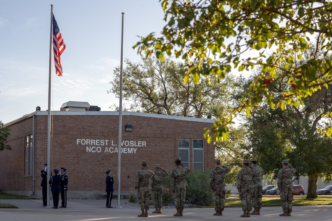 High Frontier Honor Guard Ceremonial Guardsman and Peterson-Schriever Garrison personnel salute the American flag.