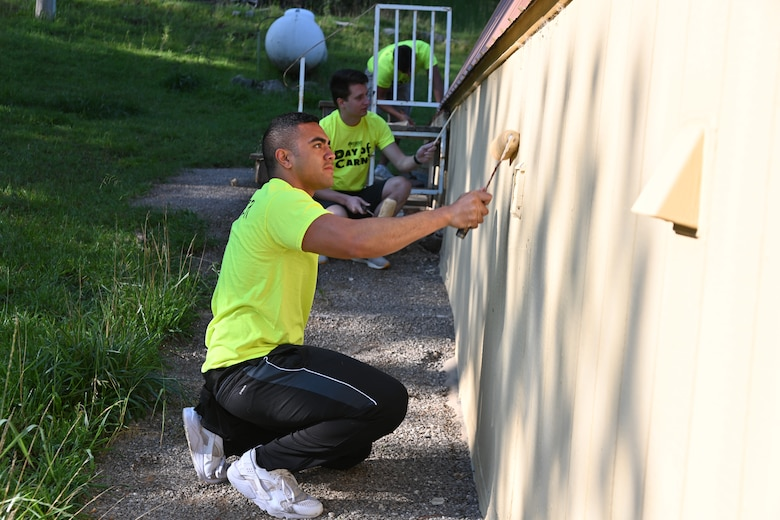 Senior Airman Ryan Lilomaiava, Day of Caring volunteer from Holloman Air Force Base, New Mexico, paints a house during the 30th annual Day of Caring, Sept. 10, 2021, in Cloudcroft, New Mexico. The Day of Caring offers support to families, disabled individuals and senior citizens within Otero County communities. (U.S. Air Force photo by Airman 1st Class Jessica Sanchez-Chen)