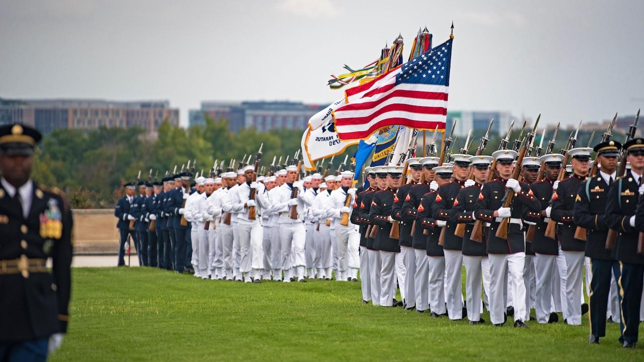Service members walk in formation on field.