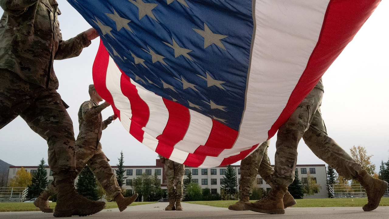 Several soldiers folding large American flag outdoors.