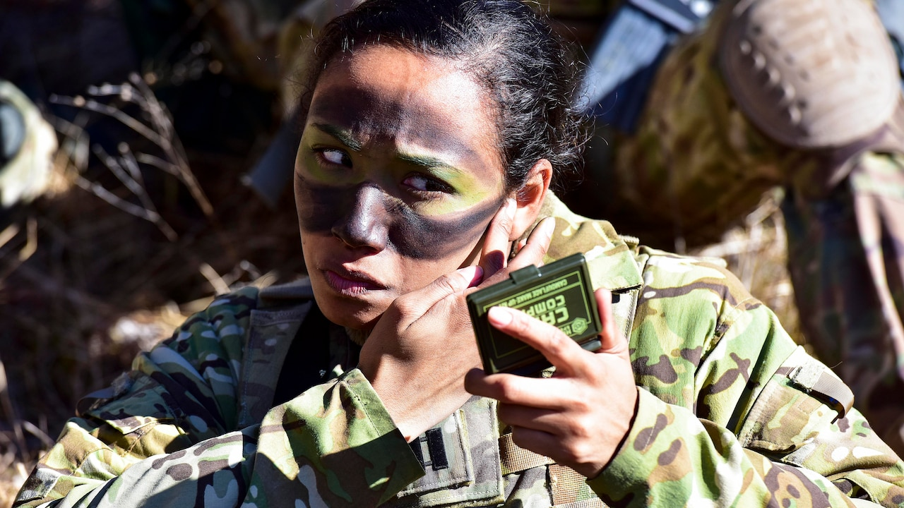 Soldier applies camouflage makeup