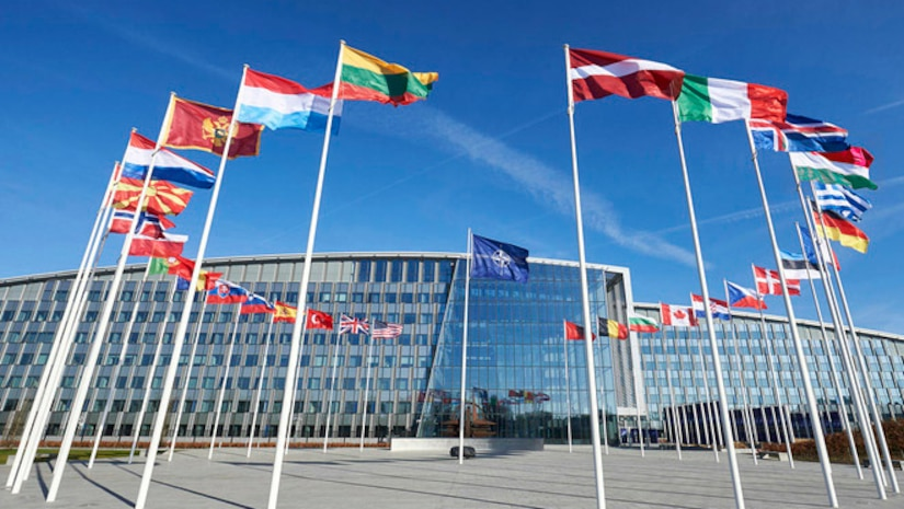 Circular display of national flags outside a glass building.