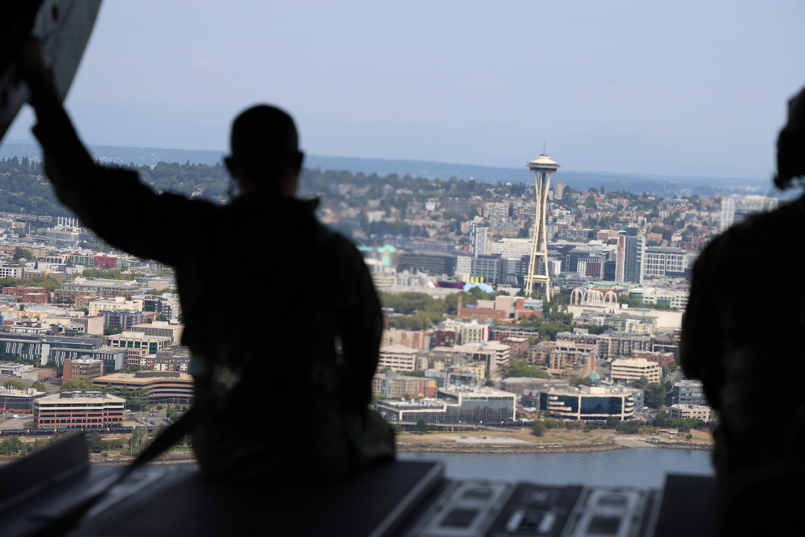 A member of the Royal Thai Army sits on the ramp of a CH-47 Chinook helicopter as it flies above Seattle, Aug. 25, 2021. The Thai Army aviators were taking part in a three-week aviation exchange with members of the Washington National Guard's 96th Aviation Troop Command.