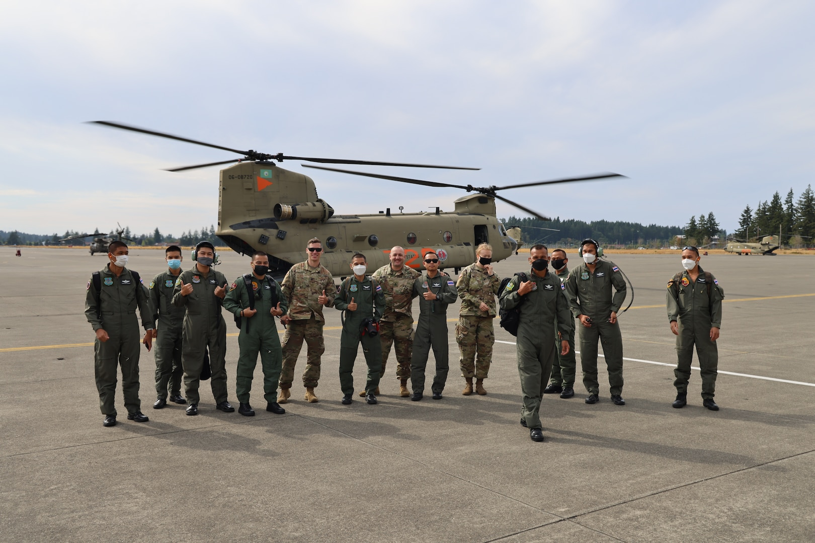 Members of the Royal Thai Army pose for a photo after a flight on a CH-47 Chinook helicopter Aug. 25, 2021 at Joint Base Lewis McChord, Washington state. The Thai Army aviators were taking part in a three-week aviation exchange with members of the Washington National Guard's 96th Aviation Troop Command.