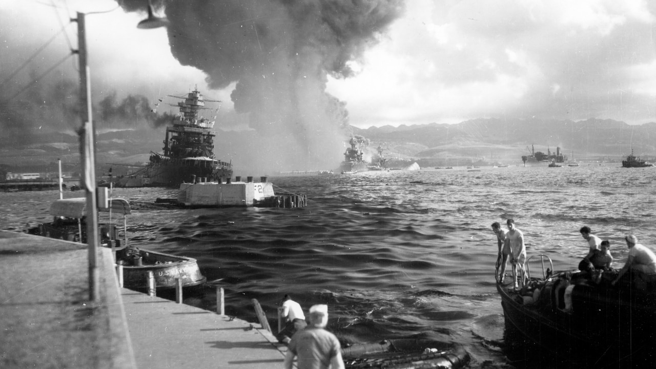 Explosion in water as troops watch.