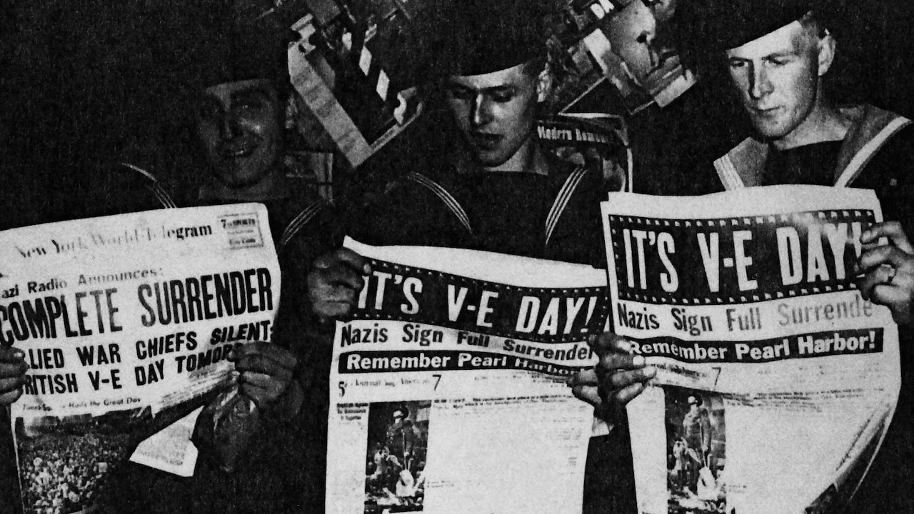 Troops reading newspapers announcing V-E Day