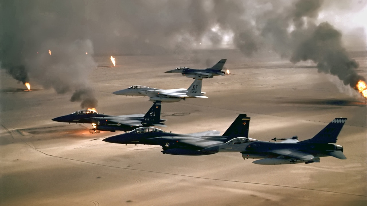Jets fly in a V as detonations light the desert below.