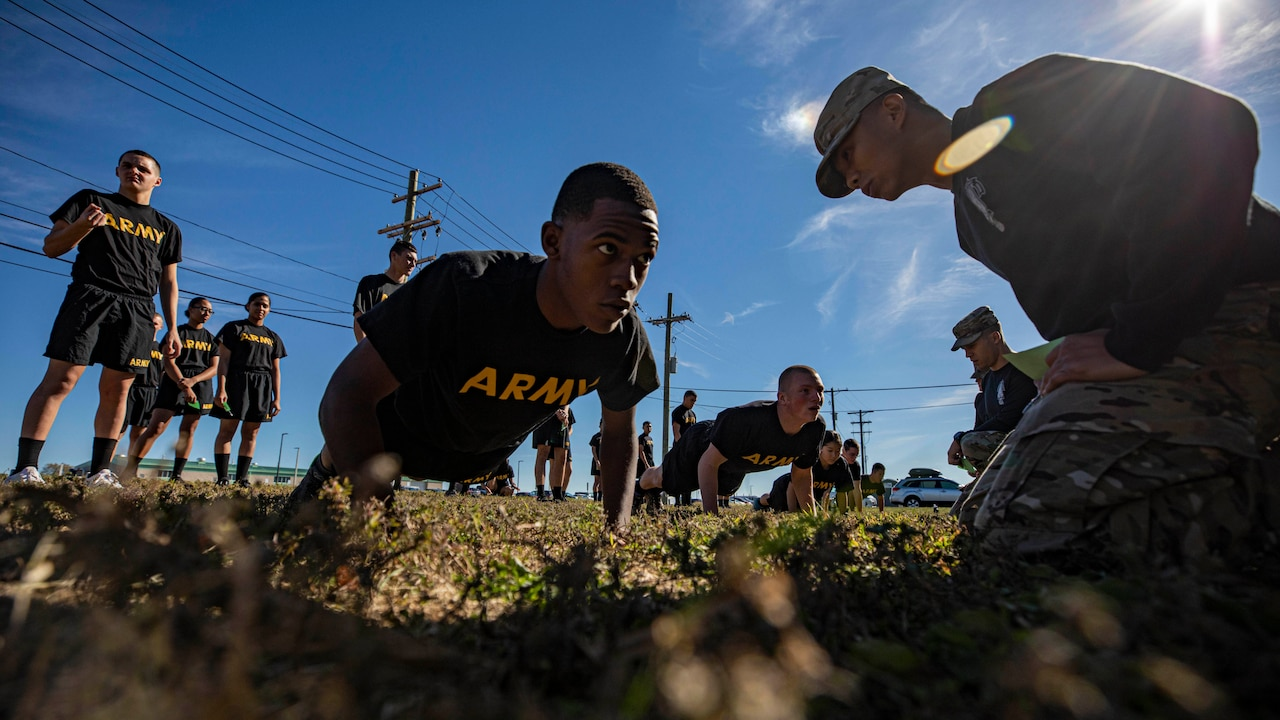 A solider does a pushup outside as others watch.