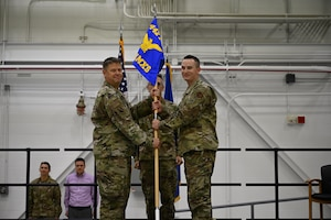 Lt. Col. William McLeod hands the 442 AMXS guidon to Maj. John Goodwin III while Erik stands at attention in civilian clothes in the background.