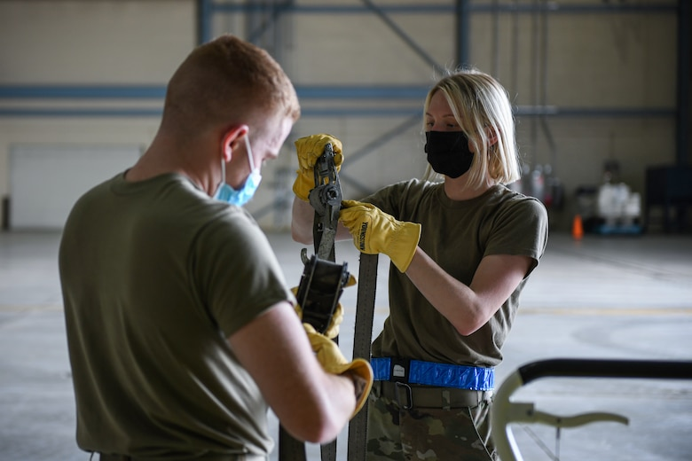 Airmen from the 319th Aircraft Maintenance Squadron roll lashing straps after disassembling a pallet of equipment during an exercise on Grand Forks Air Force Base, N.D., Aug. 18, 2021. The exercise was a joint effort with the 319th Logistic Readiness Squadron and 319 AMXS, each unit palletized their designated equipment as if they were tasked to deploy. (U.S. Air Force photo by Airman 1st Class Ashley Richards)