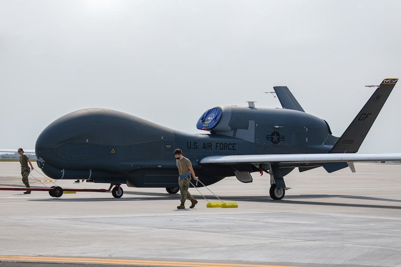 Crew chiefs assigned to the 319th Aircraft Maintenance Squadron, pull chocks beside an RQ-4 Global Hawk as it's towed across the flight line during an exercise on Grand Forks Air Force Base, N.D., Aug. 19, 2021. The primary goal of this exercise was to accelerate change in the RQ-4 enterprise and to prove the Global Hawks can meet demands of the Agile Concept Employment concept for future operations. (U.S. Air Force photo by Airman 1st Class Ashley Richards)