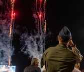 A photo of a military member watching fireworks.