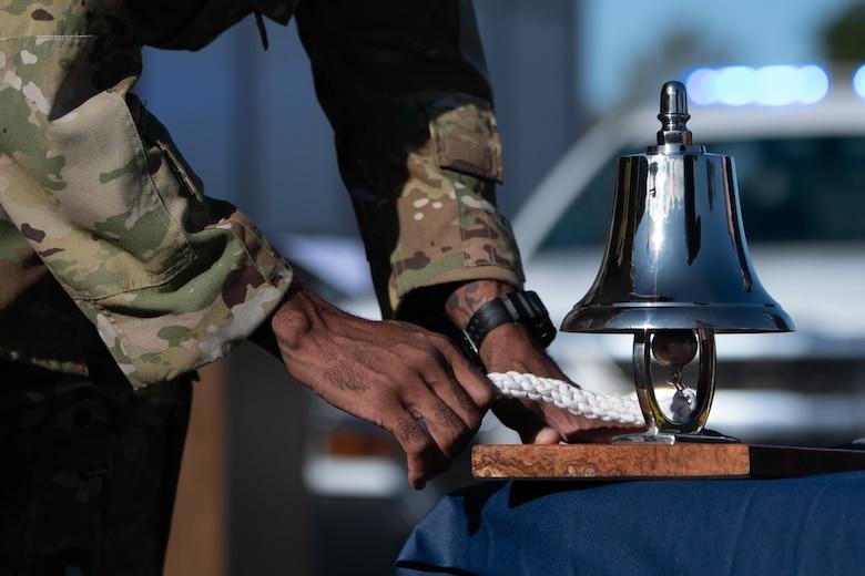 Airman ringing ceremonial bell