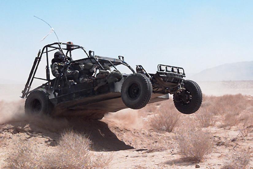 A dune buggy rolls over a sand berm.