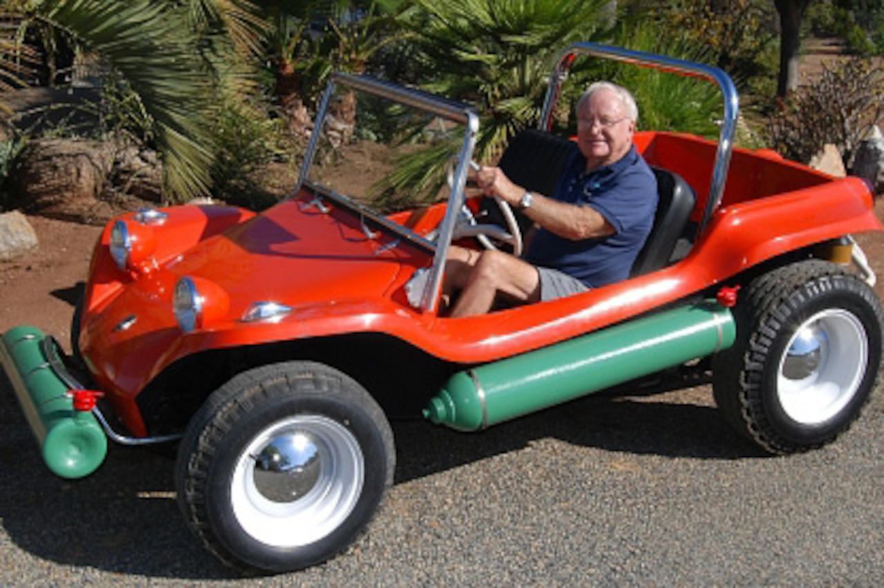 A man sits in a dune buggy.