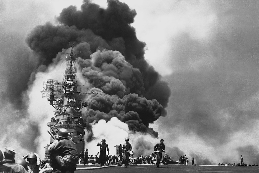 An aircraft carrier goes up in smoke.