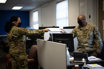 U.S. Air Force Airman 1st Class Helbees Tawadrous, a 354th Contracting Squadron (CONS) contracting specialist, left, hands a document to Tech. Sgt. Justin Williams, the 354th CONS simplified acquisitions team lead, on Eielson Air Force Base, Alaska, Sept. 8, 2021.