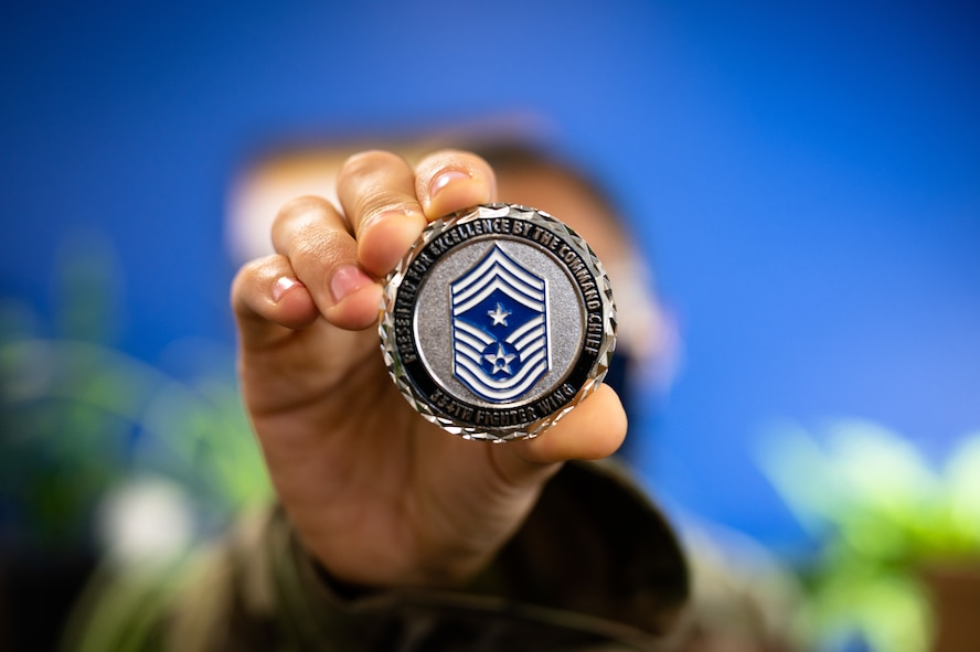U.S. Air Force Airman 1st Class Helbees Tawadrous, a 354th Contracting Squadron contracting specialist, holds out a 354th Fighter Wing command chief coin on Eielson Air Force Base, Alaska, Sept. 8, 2021.