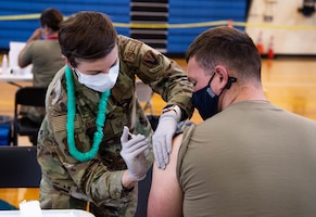Tech. Sgt. Abigail Johannesson, 692d Intelligence Reconnaissance Surveillance Group noncommissioned officer-in-charge of medical operations, administers a Covid-19 vaccine to Senior Airman Andrew Parker, 647th Civil Engineer Squadron pest management apprentice, in the Hickam Gymnasium at Joint Base Pearl Harbor-Hickam, Hawaii, Sept. 8, 2021. The vaccination clinic supported a Department of Defense priority of vaccinating every eligible Service member to improve readiness and positively impact their families, neighbors, and communities in which they serve. (U.S. Air Force photo by Senior Airman Alan Ricker)