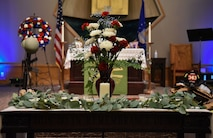 A table is decorated with a bouquet of red and white flowers, with candles and leaves.