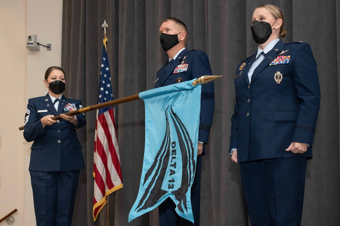 Brig. Gen. Shawn Bratton, Space Training and Readiness Command commander, and Col. Niki Lindhorst, Air University space chair, stand at attention as Chief Master Sgt. Esther Sanford unfurls the Space Delta 13 flag during the unit's activation ceremony at Officer Training School, Sep. 13, 2021.