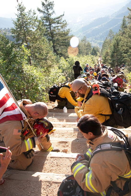 Firefighters kneel on the Manitou Incline