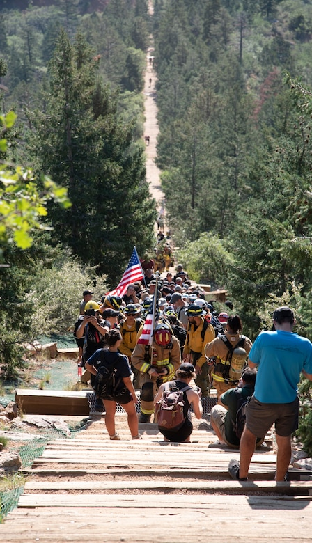 Firefighters from over 200 local and out-of-state fire stations kneel during a moment of silence while climbing up Manitou Incline.