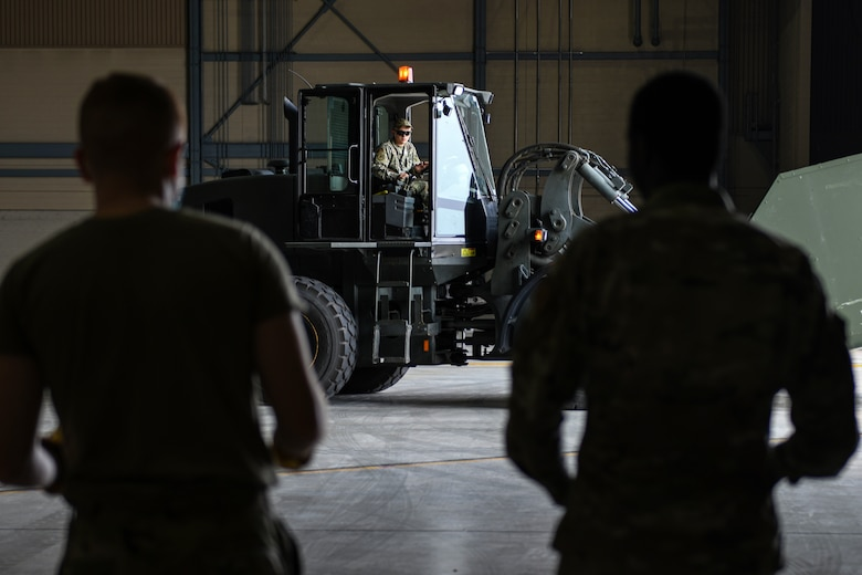 Airmen from the 319th Aircraft Maintenance Squadron watch as Staff Sgt. Thomas Anastasia, 319th Logistic Readiness Squadron vehicle operator, as he drives a forklift carrying equipment used during an exercise on Grand Forks Air Force Base, N.D., Aug. 18, 2021. A total of 768 items were transported throughout the exercise weighing in at approximately 153,884 pounds. (U.S. Air Force photo by Airman 1st Class Ashley Richards)