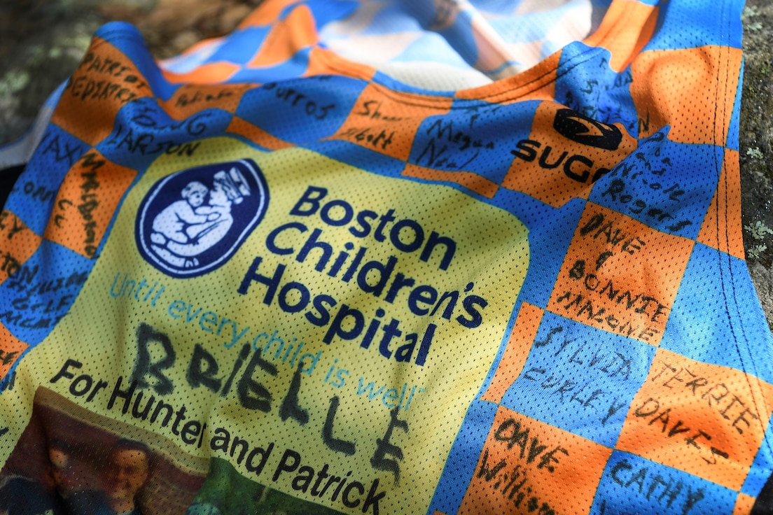 Sponsor signatures cover the Boston Marathon jersey front of Maj. Kristopher Williams, Kill Chain Integration Branch chief, outside Hanscom Air Force Base, Mass., Sept. 8. Williams will participate in the Oct. 11 race as part of the Boston Children's Hospital marathon team, and will represent two child patients, Patrick, 15, from Burlington, Mass., and Hunter, 6, a Hanscom resident. (U.S. Air Force photo by Lauren Russell)