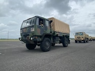 Light Medium Tactical Vehicles (LMTV) assigned to the Louisiana National Guard's 527th Engineer Battalion, 225th Engineer Brigade, lead a convoy of dump trucks and flat-bottom boats to be staged in advance of Tropical Storm Nicholas at the Burton Coliseum in Lake Charles, Louisiana, Sept. 13, 2021.