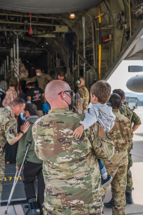 An airman carries a child onto a large military aircraft.