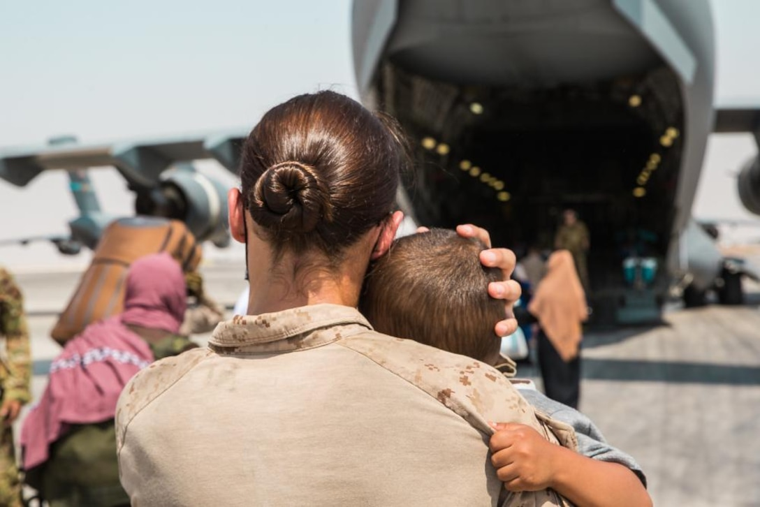 U.S. Marine Corps Cpl. Caitlin McCormick, an Evacuation Control Center Marine, carries a child to a plane at Al Udeid Air Base, Qatar, Sept. 1, 2021. The Department of Defense is committed to supporting the evacuation of American citizens, Special Immigrant Visa applicants and other at-risk individuals from Afghanistan.