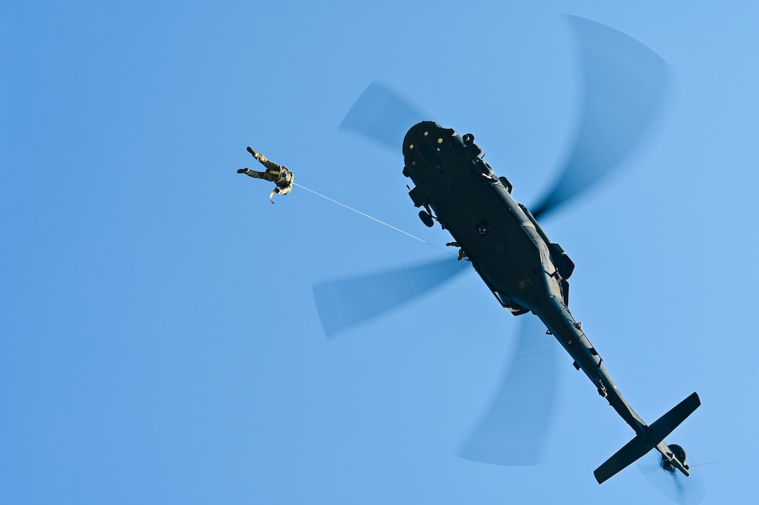 two military members hang from helicopter