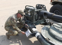 """Staff Sgt. Jeremy Driscoll, the air noncommissioned officer in charge with the Fort Bragg, N.C., based 3rd Battalion, 319th Airborne Field Artillery Regiment, 1st Brigade Combat Team, 82nd Airborne Division, verifies documentation on one of the battalion's M119 howitzers during a survey of gear collected and secured by the 401st Army Field Support Brigade in one of their lots at Camp Arifjan, Kuwait, Sept. 1, 2021. Driscoll and his fellow """"Gun Devils"""" deployed to Kabul's Hamid Karzai International Airport during Operation Allies Refuge to support evacuation operations as the U.S. military ended operations in Afghanistan."""