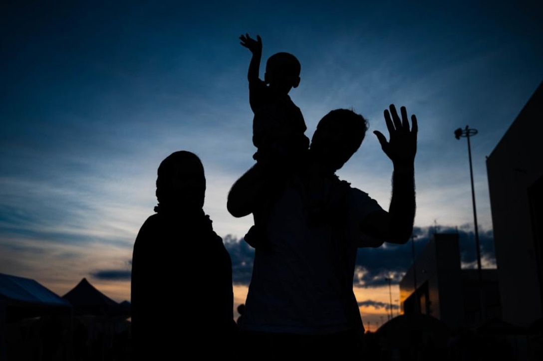 A silhouette of two adults and a child.