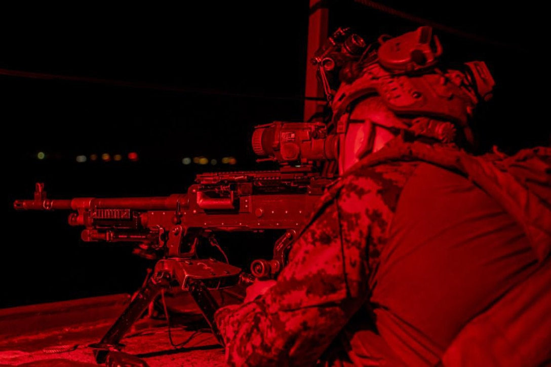 A Marine bathed in red light looks through his gun scope at night.