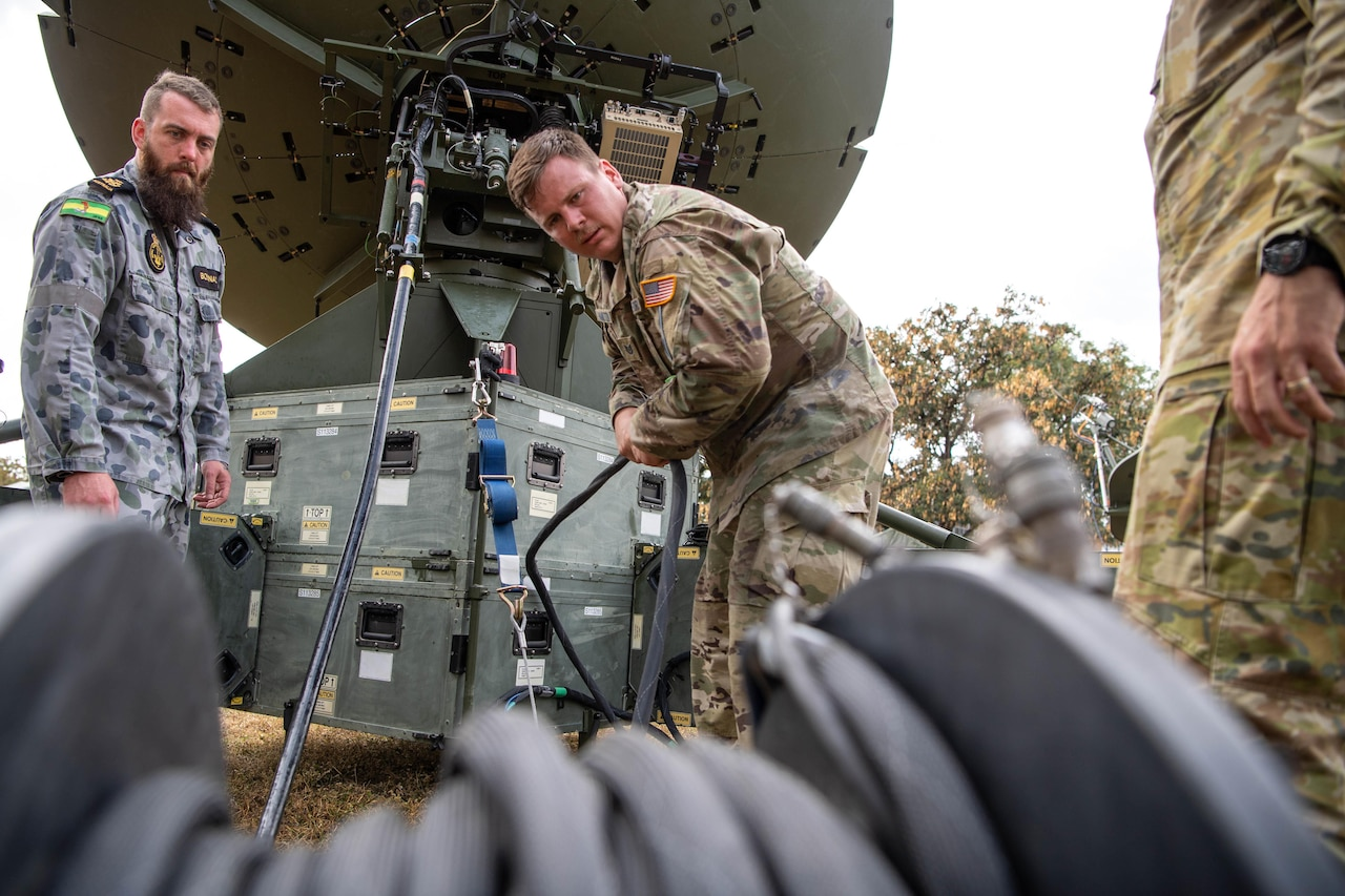 Men work on satellite communications.