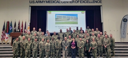 """Fully-vaccinated in-person attendees, who wore masks during the three-day hospitalization summit as an extra COVID-19 precaution, pose for a quick """"mask-off"""" group photo with J.M. Harmon III (center), deputy to the commanding general, U.S. Army Medical Center of Excellence, on Sept. 10 in Blesse Auditorium at Joint Base San Antonio-Fort Sam Houston."""