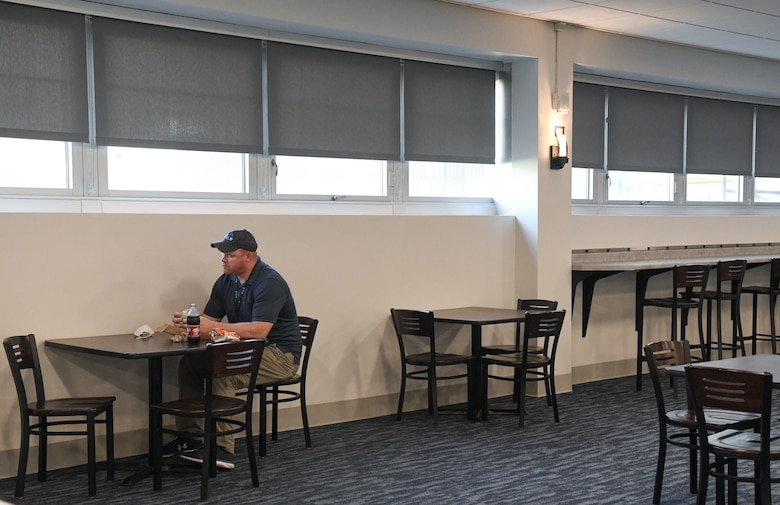Sterling Price, an Arnold Engineering Development Complex network engineer, dines in the newly-renovated Café 100, Sept. 9, 2021, at Arnold Air Force Base, Tenn. In the right of the photo, counter-height seating with electrical outlets for charging electronics can be seen, one of the additions made to the seating area. (U.S. Air Force photo by Jill Pickett)