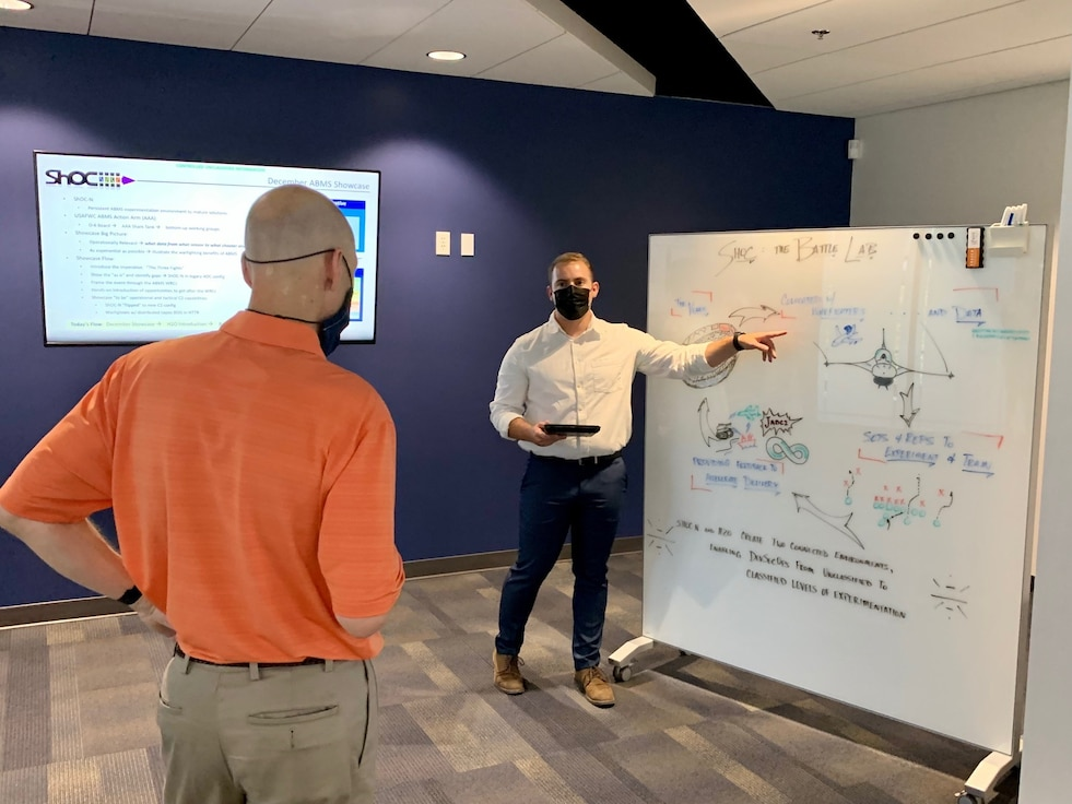 Photo of man briefing another man in front of whiteboard