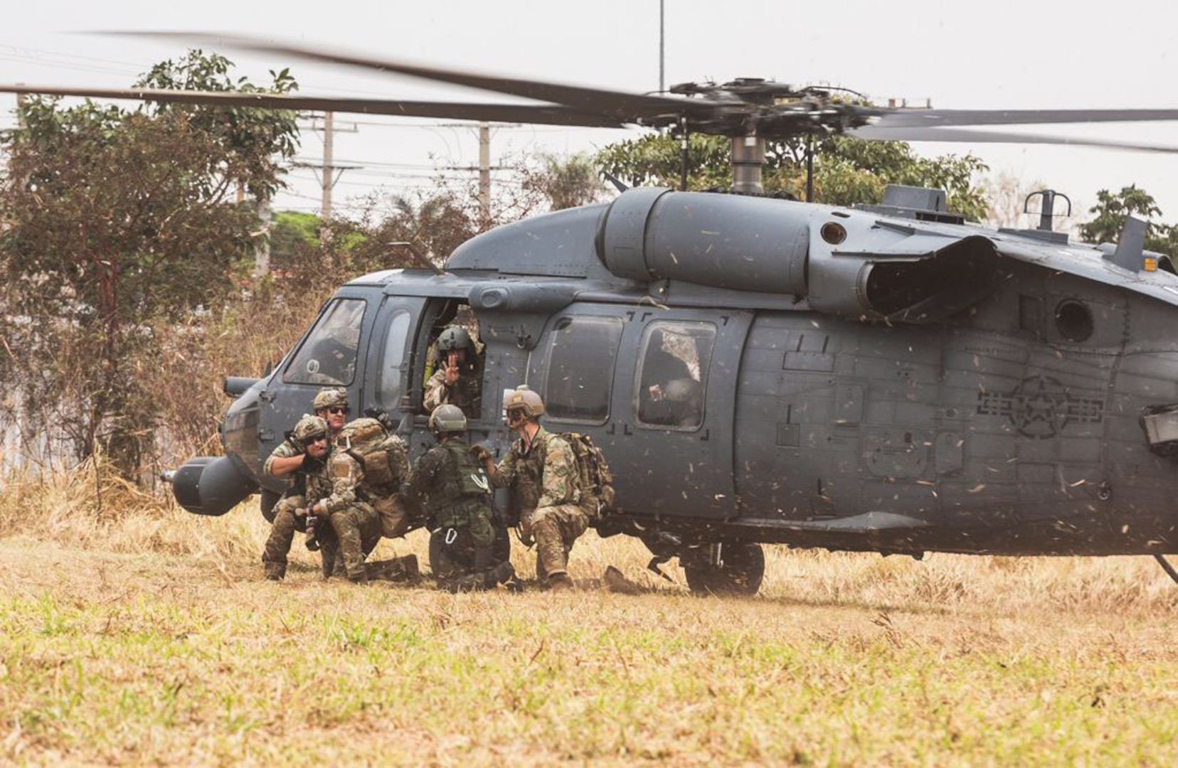 Brazilian airmen and pararescue Airmen from the New York Air National Guard's 106th Rescue Wing exit an HH-60 Pave Hawk  while participating in Exercise Tapio 2021 at Campo Grande Air Base, Campo Grande, Brazil. The exercise Aug. 19-31 was part of the National Guard's State Partnership Program.