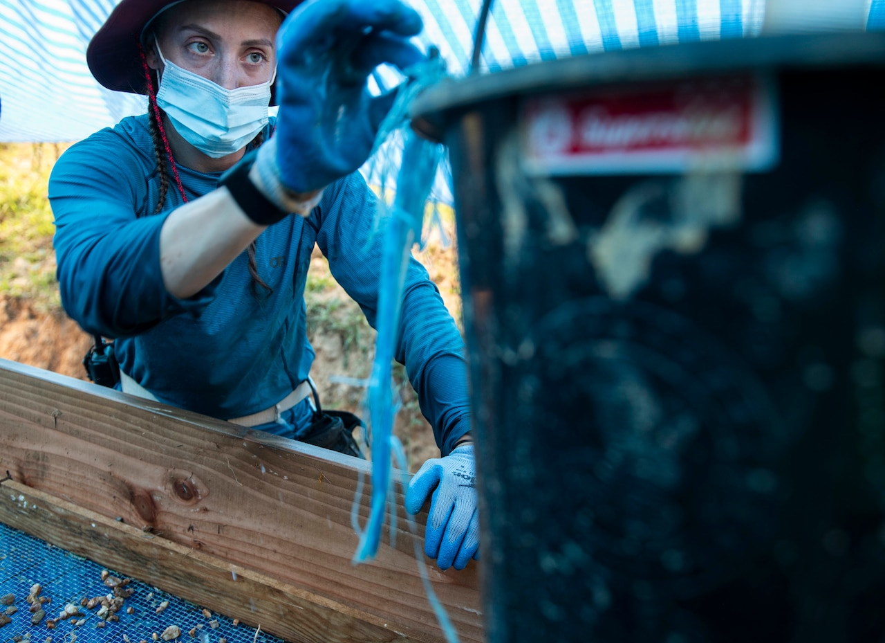 A solider puts materials in a bucket.