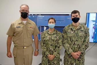 DAHLGREN, Va. (Sept. 10, 2021) Instructor Fire Controlman (Aegis) 1st Class Kirt Palmer (right) and student Fire Controlman (Aegis) 3rd Class Felice Hahn (center) execute an Aegis Virtual Maintenance Trainer (VMT) demonstration for Commander, Navy Regional Maintenance Center (CNRMC) and Director, Surface Ship Maintenance, Modernization and Sustainment (SEA 21), Rear Admiral Eric Ver Hage (left), during his tour at the AEGIS Training and Readiness Center (ATRC), onboard Naval Support Facility (NSF) Dahlgren, Sept. 10. (U.S. Navy photo by Michael Bova)