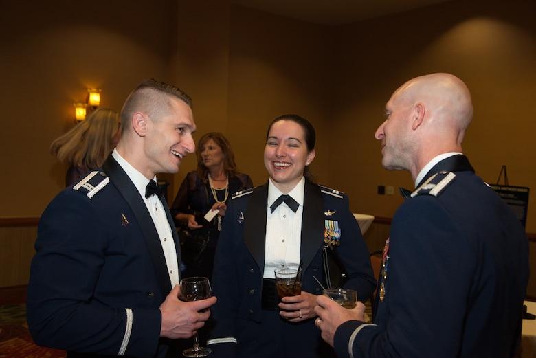 Military members talk during annual NDIA ball where one was honored.
