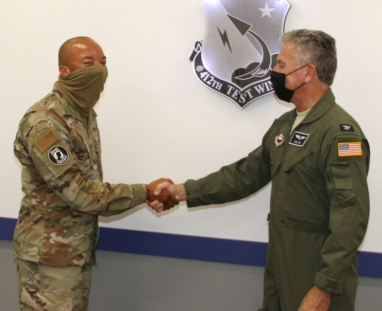 ol. Randall Gordon (left), vice commander, 412th Test Wing, shakes hands with Col. Ross Veta, California Wing commander