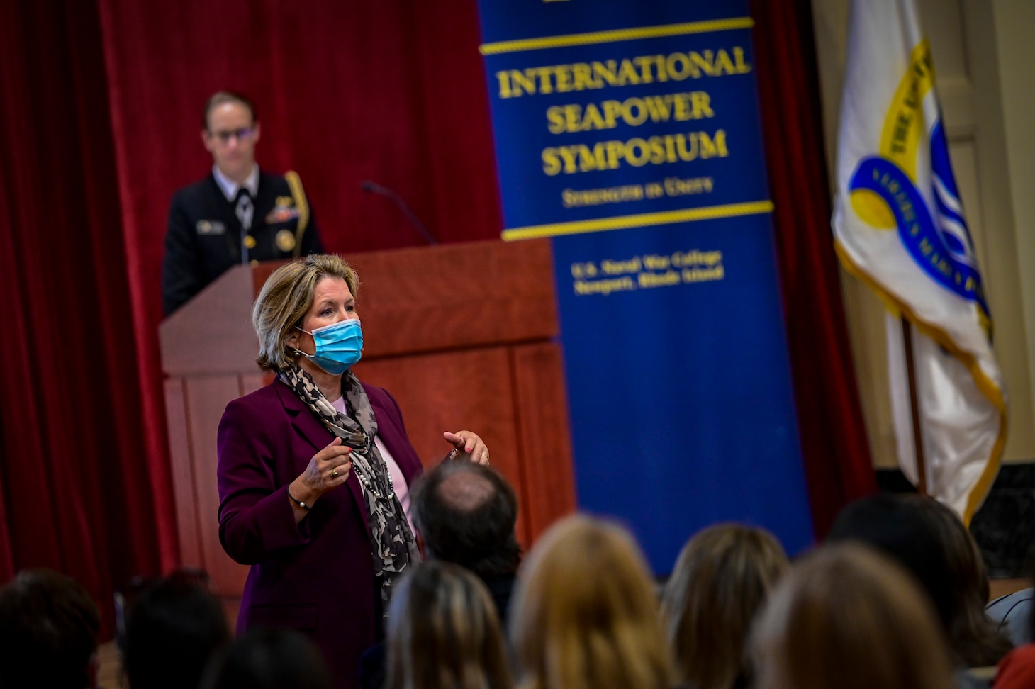 """A woman wearing a blue face mask in a red blazer address a crowd in an auditorium, while another woman in uniform stands behind a podium. A banner in the background reads """"International Seapower Symposium."""""""
