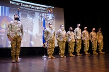 """U.S. Air Force Airmen from the 375th Communications Support Squadron receive an Air Force Achievement Medals in the Base Auditorium at Scott Air Force Base, Ill., September 2, 2021. The individuals photographed are members of what is called """"Tether Team"""" are programmers and software and application developers who recently were recognized for their contributions in Operation Allies Refuge. (U.S. Air Force photo by Staff Sgt. Dalton Williams)"""